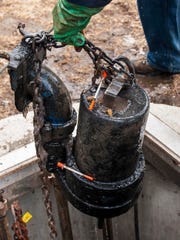 A pump fouled with hypodermic needles and wipes is pulled from a wastewater pumping station on Pine Street in Burlington Tuesday. The wipes have clogged pumps, pipes and other parts of the city's wastewater infrastructure. This particular pumping station, with two pumps, is cleaned weekly.