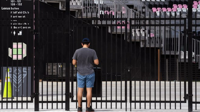 Harold Garcia of Fort Lauderdale looks in on a closed Inter Miami CF Stadium on Saturday, the day David Beckham's team, Inter Miami, was to make its home debut. The match against the L.A. Galaxy was postponed due to the coronavirus pandemic.