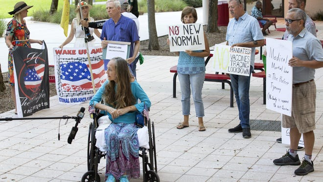 A group of opponents of the wearing of masks surround one of their group while she is interviewed by a local TV station before the Palm Beach County commission meeting on June 23 in which commissioners unanimously voted to require people to wear masks in public.