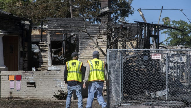 A PG&E crew surveys one of five homes destroyed in a fast-moving grass fire that spread to buildings on North Stanford Avenue in Stockton on Sunday.