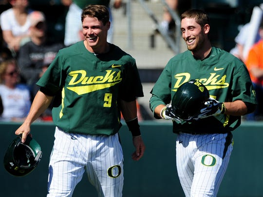 Oregon's Brandon Cuddy, right, celebrates his two-run home run with Scott Heineman (9) against Oregon State at PK Park, on Sunday, April 12, 2015, in Eugene. Oregon won the game 10-9.