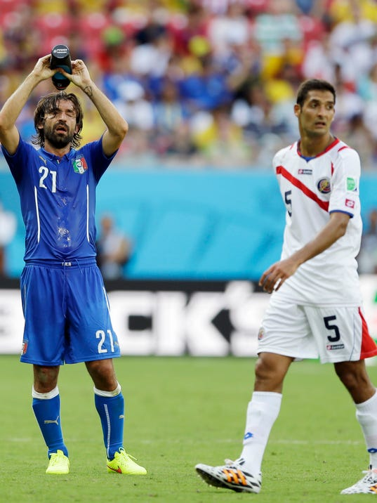 Costa Rica's Celso Borges, right, waits for play to resume as Italy's Andrea Pirlo cools off with water during the group D World Cup soccer match between Italy and Costa Rica at the Arena Pernambuco in Recife, Brazil, Friday, June 20, 2014.  (AP Photo/Ricardo Mazalan)