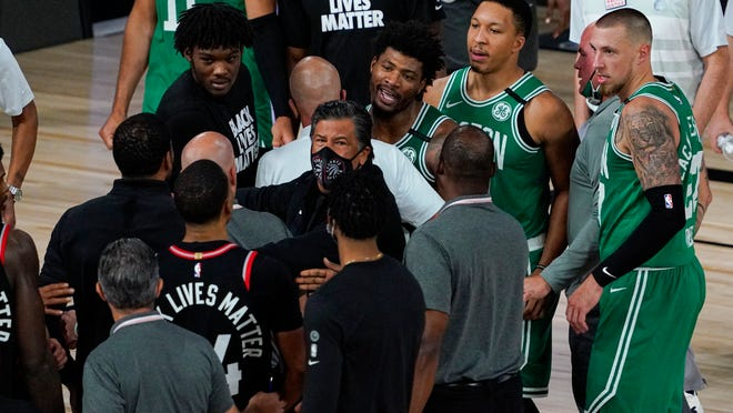 Boston Celtics guard Marcus Smart (36) exchanges works with members of th eToronto Raptors following an NBA conference semifinal playoff basketball game Wednesday, Sept. 9, 2020, in Lake Buena Vista, Fla. The Raptors defeated the Celtics 125-122.