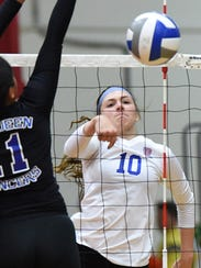 Reno senior Parker Buddy spikes the ball as McQueen's