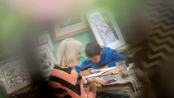 Art teacher Vivian Dwyer sits with Max Boyang, 10, as he works on a painting on Wednesday, May 4, 2016 at Arty Party Studio in Okemos. Dwyer described Boyang's style of art as abstract with his use of patterns. He and his twin brother Louis are having an art show at the studio from May 15- May 19. All proceeds will go to Joey's Wings Childhood Cancer Foundation.