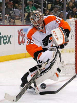 Philadelphia Flyers goalie Steve Mason (35) clears the puck during the second period of an NHL hockey game against the Pittsburgh Penguins in Pittsburgh, Saturday, April 12, 2014. (AP Photo/Gene J. Puskar)