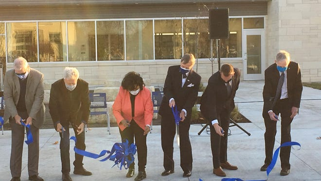 Washburn University President Jerry Farley and other WU officials cut the ribbon with over-sized scissors, christening the school's new indoor athletic facility Thursday.