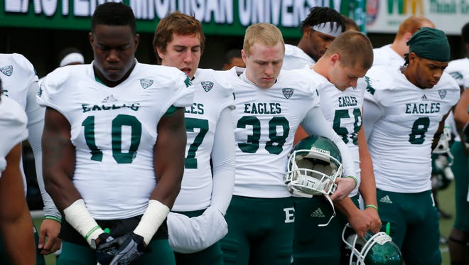 Members of the Eastern Michigan football team observe a moment of silence for their fallen teammate Demarius Reed, who was found shot to death early Friday, Oct. 18.