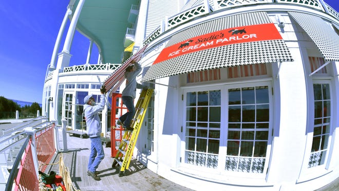 Doug Saul, left, and Jason Barnes of Advanced Awnings place an ice cream parlor awning at Mackinac Island's Grand Hotel.