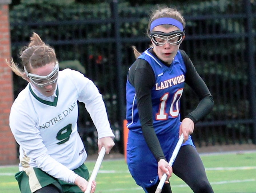 Ladywood's Abby Randall (right) tries to pick up the ground ball in Tuesday's 10-9 victory over Ann Arbor Gabriel Richard.