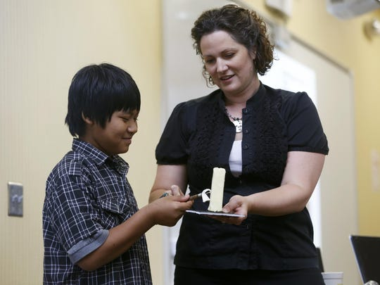 Lay Kbaw, 12, slices into a stick of butter held by Sarah Pratt, the sculptor of the Iowa State Fair Butter Cow, on June 25, 2015, as Pratt helps kick off a state fair-themed language fair during an English Language Learners summer school program at Meredith Middle School in Des Moines.