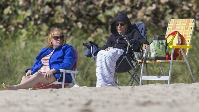 South Florida could see chillier temperatures this week. Trish Aubin (left), of Connecticut, and her friend, Jennie Quirk, of West Palm Beach, paid a visit to o the Lake Worth municipal beach during a cold snap in 2016.