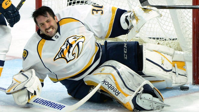 Predators goalie Carter Hutton falls to the ice after making a save and getting his helmet ripped off against the Senators.