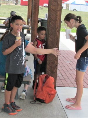 Aydin Adeleke of Solon enjoys an ice cream cone his cousin Keira Howard (right) of Wooster bought for him at the Holmes County Fair.