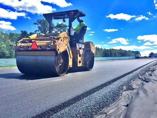 A top coat layer of asphalt is compacted earlier this