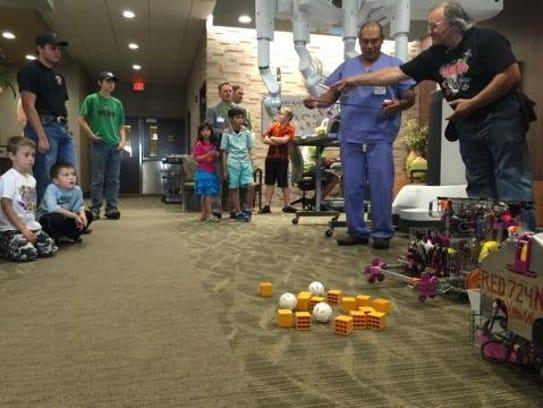 Sun River Robotics Coach Chuck Merja talks to Vic Bonilla,