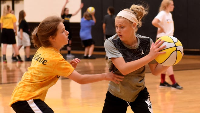 Seventh-graders Alex Nickel and Kalleigh Rennie run a drill practicing a flex offense during a youth basketball camp at Watkins Memorial High School on Monday, June 5, 2017.