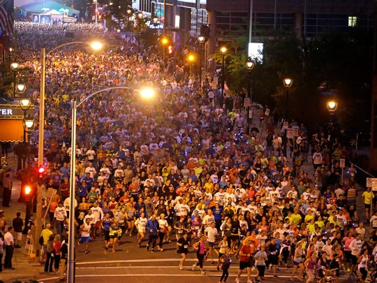 Thousands of runners storm the Bastille on Jefferson St. at the start of the 5K runs during  Bastille Days, Milwaukee's annual French-themed festival on July 9, 2015.