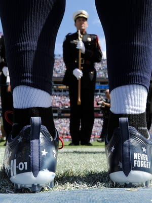 Titans inside linebacker Avery Williamson (54) wears his patriotic 9/11 cleats at the start of the home opener against the Vikings.