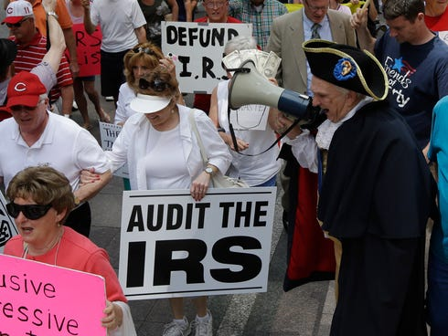 Tea party activists march from Fountain Square to the John Weld Peck Federal Building, May 21, 2013, in Cincinnati.