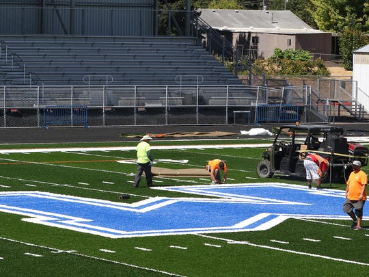 Workers install turf on Thursday, Aug. 20, 2015, at McNary High School's football field in Keizer.