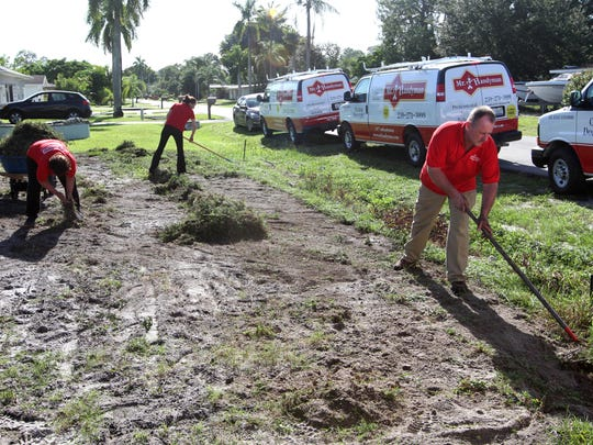 Gerry Reid, right, Samantha Cassaday, and Linda Conklin, of Mr. Handyman, work to remove the old grass from the yard of veteran Doug Hale in preparation for new sod during a National Day of Service on Wednesday.