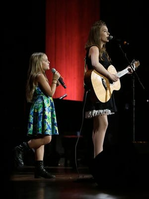 "Lennon, right, and Maisy Stella, left, perform during the Americana Music Honors and Awards show in this 2013 file photo taken in Nashville, Tenn. HarperCollins Publishers announced Friday that the young Stella sisters, stars of the TV series ""Nashville,"" are working on the picture book ""In the Waves."""