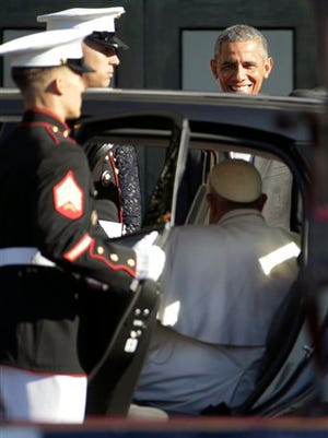 President Barack Obama greets Pope Francis as he arrives in Fiat 500L for a state arrival ceremony, Wednesday, Sept. 23, 2015, on the South Lawn of the White House in Washington. (AP Photo/Pablo Martinez Monsivais)