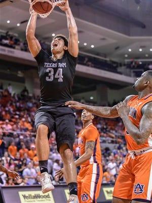 Texas A&M center Tyler Davis (34) dunks the ball over Auburn forward Cinmeon Bowers (5) during the first half of an NCAA college basketball game, Tuesday March 1, 2016, in Auburn, Ala.