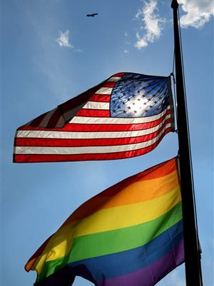 The American and gay pride flags fly at half-mast over the LGBT Community Center of Central Florida, Monday, June 13, 2016. The Center is a gay-rights support group in Orlando, located about 4 miles from the Pulse nightclub where the massacre occurred on Sunday.  (Joe Burbank/Orlando Sentinel via AP)