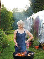 "This undated photo provided by Clarkson Potter/Penguin Random House shows Erin French, owner of The Lost Kitchen restaurant in Freedom, Maine, grilling burgers with an Airstream trailer in the background. French has just come out with a cookbook called ""The Lost Kitchen"" that tells the remarkable story of her career from a teenager working in her dad's diner to giving dinner parties in her apartment and later in an Airstream, to running a wildly successful 40-seat restaurant in an old mill in a tiny Maine town."