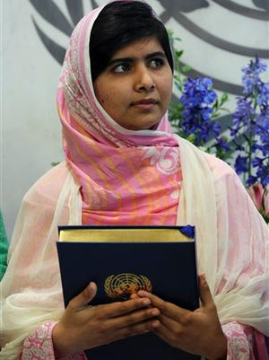 """FILE- In this file photo dated Friday, July 12, 201,  Malala Yousafzai holds a copy of the United Nations charter presented to her by Secretary-General Ban Ki-moon, at United Nations headquarters.  Malala Yousafzai, the Pakistani teenager shot by the Taliban for promoting education for girls, celebrated her 16th birthday on Friday addressing the United Nations. Teenage activist Malala Yousafzai has jointly won the Nobel Peace Prize for her """"heroic struggle"""" for girls' rights to education, it is announced Friday Oct. 10, 2014.  (AP Photo/Mary Altaffer, FILE)"""