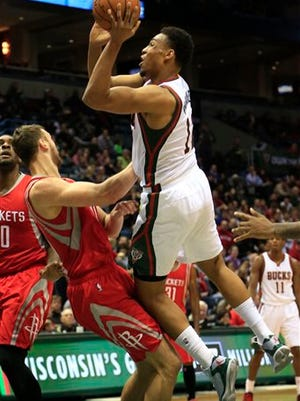 Milwaukee Bucks forward Jabari Parker, right, goes up for a basket against Houston Rockets forward Donatas Motiejunas, left, during the second half of an NBA basketball game Saturday, Nov. 29, 2014, in Milwaukee. (AP Photo/Darren Hauck)