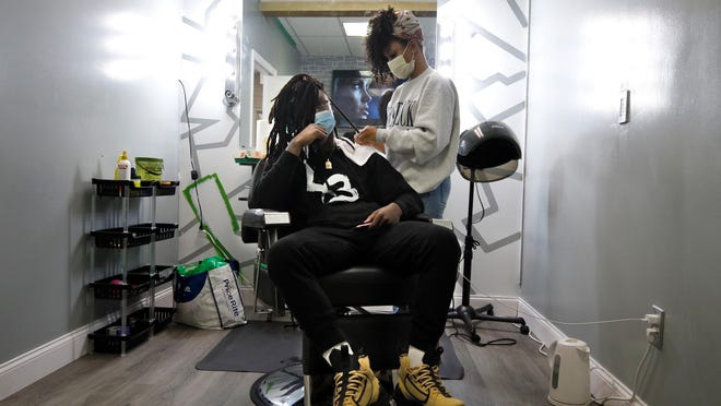 P.G. Wehjla watches a movie in the single-chair braiding room at Barbershop Love in North Providence as hairstylist Yamely Alvarez re-twists his dreadlocks Monday afternoon. The barbershop reopened Monday, having shut down in compliance with the state's coronavirus restrictions in March.