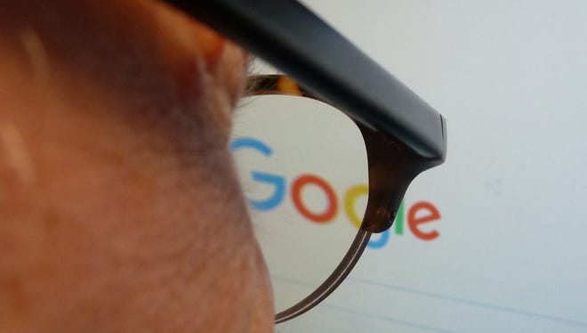 A journalist looks at the new Google logo at his work station in Washington, DC on September 1, 2015. Google on Tuesday refreshed its logo to better suit mobile devices that are supplanting desktop computers when it comes to modern Internet lifestyles.