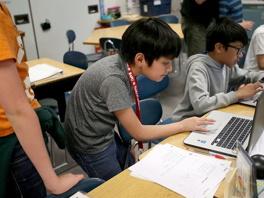 SWAT team member Ethan Jingco, 11, (center) helps a fellow student with his computer during class at Emerald Heights Elementary School in Silverdale on May 10.
