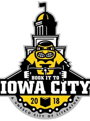 """Iowa City's theme for the RAGBRAI overnight stop is """"Book it to Iowa City,"""" a nod to the city's designation as a UNESCO City of Literature. The logo depicts Herky the Hawkeye riding a bike in front of the Old Capitol."""