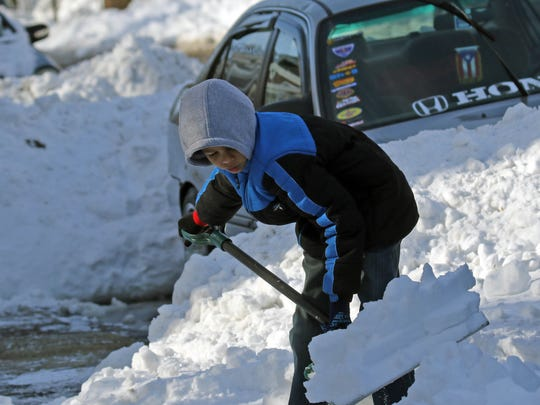 9 year-old Jahkai Gray helps shovel out his families vehicles along the 2800 block of Washington Street on Monday morning.