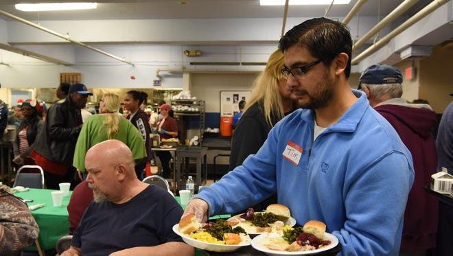 Volunteer Tim Gonzalez serves patrons at the annual Eileen Hickey Holiday Dinner. on Dec. 25, 2015.