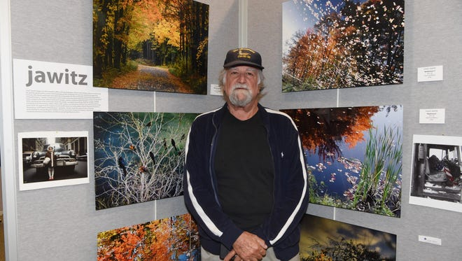 Airman Louis Jawitz, 74, a U.S. Navy veteran, poses with some examples of his photography on display at the Veteran Arts Showcase at the Franklin D. Roosevelt Presidential Library and Museum in Hyde Park.