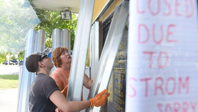 Tanner (left) and Debbie Hrobak, of Port St. Lucie, install storm shutters ahead of Hurricane Matthew on Wednesday, Oct. 5, 2016, at Billy Bones Bait-N-Tackle South in Stuart.