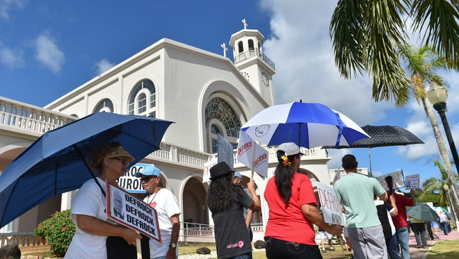 Members and supporters of the Laity Forward Movement and the Concerned Catholics of Guam protest against Archbishop Anthony Apuron at the Dulce Nombre de Maria Cathedral Basilica in Hagåtña on June 4, 2017.