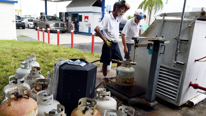"""Ruben Morales wipes the sweat from his brow as he and fellow employee Doug Mull fill propane tanks Tuesday, Sept. 5, 2017, at the Steil gas station in Vero Beach. """"We have two 800-gallon propane tanks and we've had to refill them five times since last Friday,"""" Morales said. Local residents are filling up fuel and food as Hurricane Irma makes its way through the Caribbean."""
