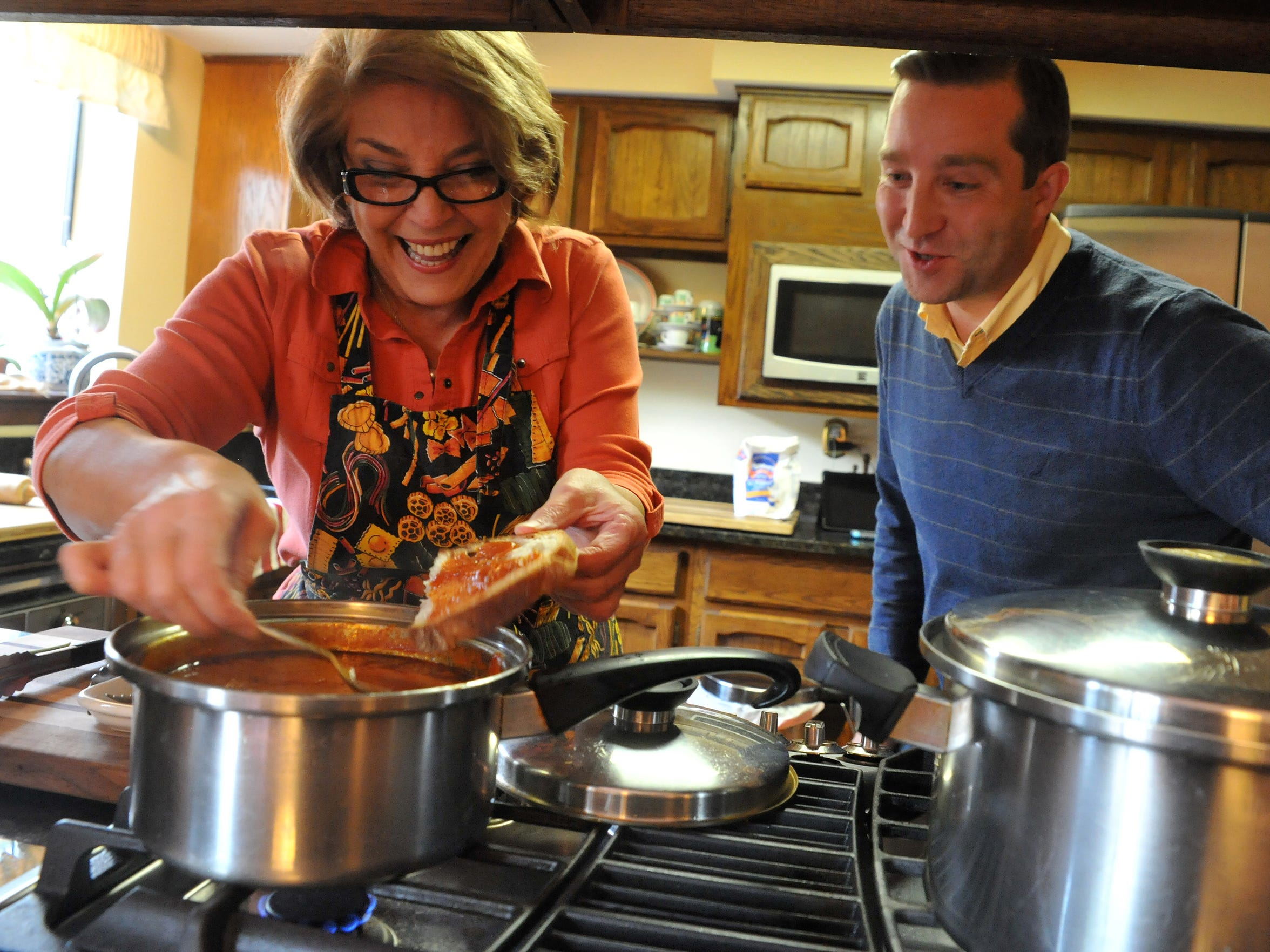 Anna DeCristofaro puts some of her homemade gravy on piece of bread for her son Giancarlo DeCristofaro, of Shamong, to snack on while she finishes making a pasta and gravy dinner for three generations of the family, Sunday,  Oct. 25 at her home in Medford.