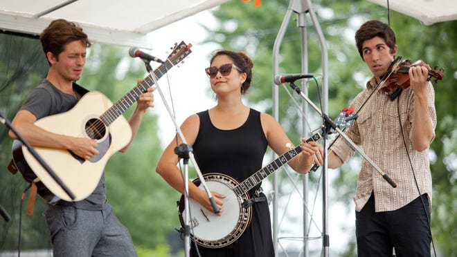 The Appleseed Collective's Andrew Brown, Katie Lee, and Brandon Smith perform on stage during Thumbfest Saturday in Lexington.