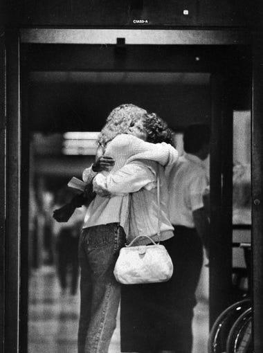 Julie Scherer, left, is hugged by a friend, Kim Hoyt,