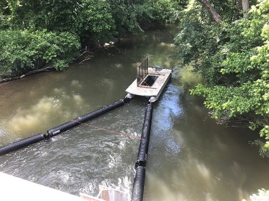 "The ""Trash Trout"" device was installed on Mud Creek to stop floating debris before it gets to the French Broad River."