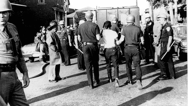 Police make an arrest during the riots in 1964.