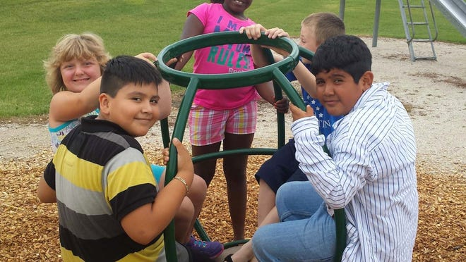 """This year, students of Parkside Elementary School were greeted back to school with two new pieces of playground equipment that were purchased from funds received from Box Top collections. Danaiyah Rhodes, back center, along with Jacob Williams (clockwise from Danaiyah), Alexander Picazo, David Javier and Sierra Heimermann test out the new """"Comet"""" playground equipment."""