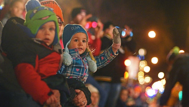 Hannah Lindner, 4, of Sioux Falls, sits on her mom, Rachel Lindner's lap while waving to parade participants during the Parade of Lights Friday, Nov. 25, 2016, along Phillips Avenue in downtown Sioux Falls.